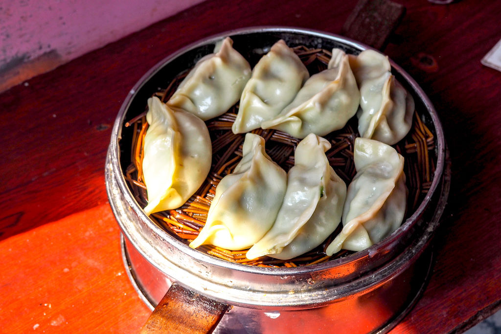 Eight pork steamed dumplings in a metal basket