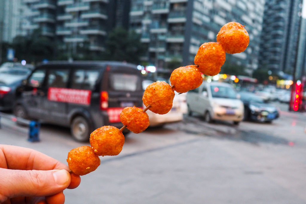 A hand holding a skewer of seven small orange puffs