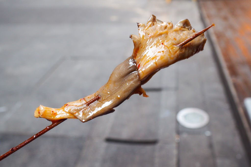 An oyster mushroom on a skewer covered in red marinade