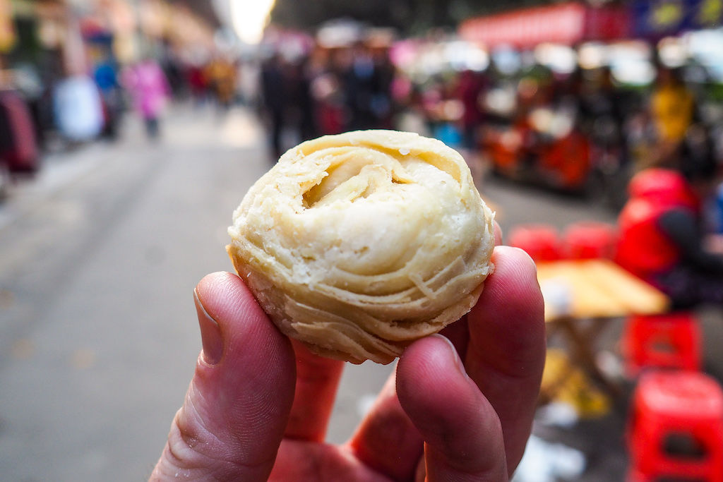 A small flaky pastry being held by a hand with the street food carts of chengdu in the background