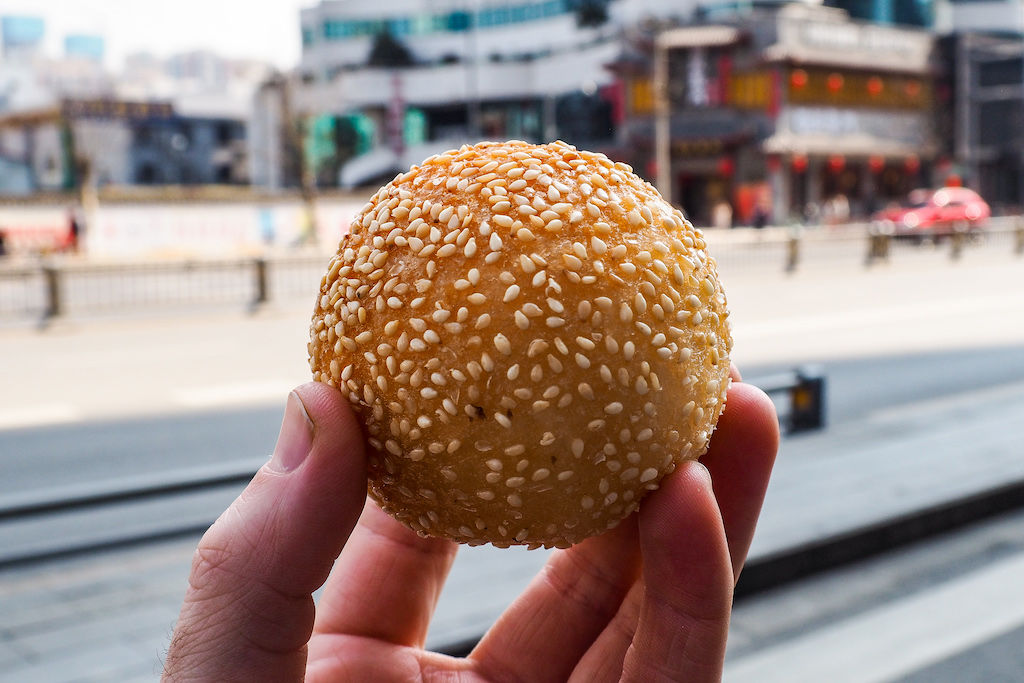 A rice cake ball that has been fried and rolled in sesame seeds being held in a hand