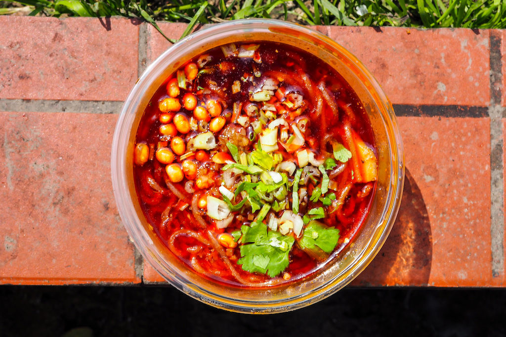 A plastic container full of Sichuan noodles, a popular street food in Chengdu