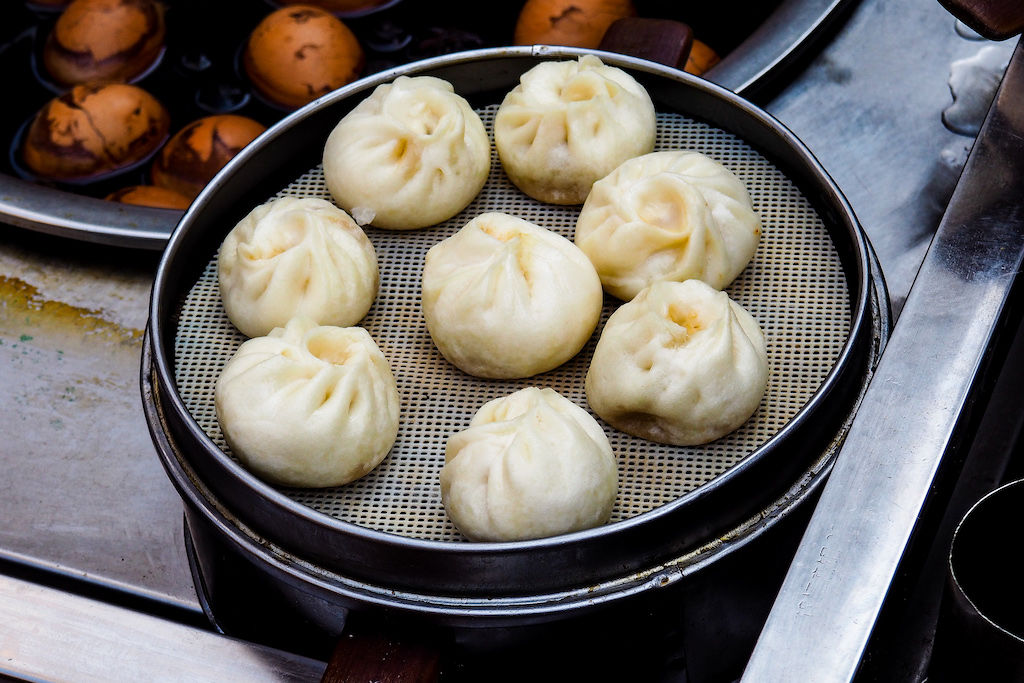 Eight pork-filled steamed buns in a metal basket