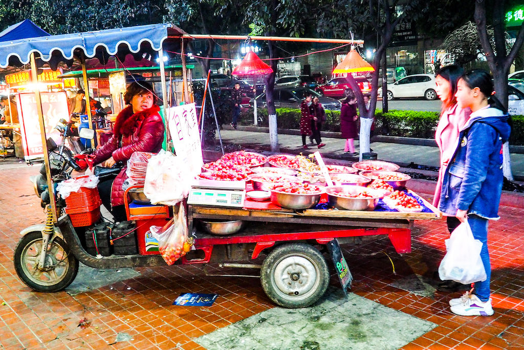 A woman serving street food out of a cart in Chengdu, China