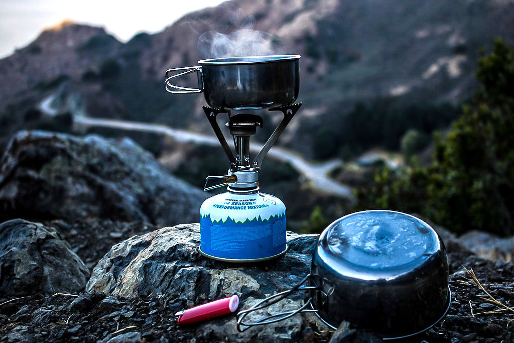 A camping stove with steam coming out of the top while cooking backpacking food
