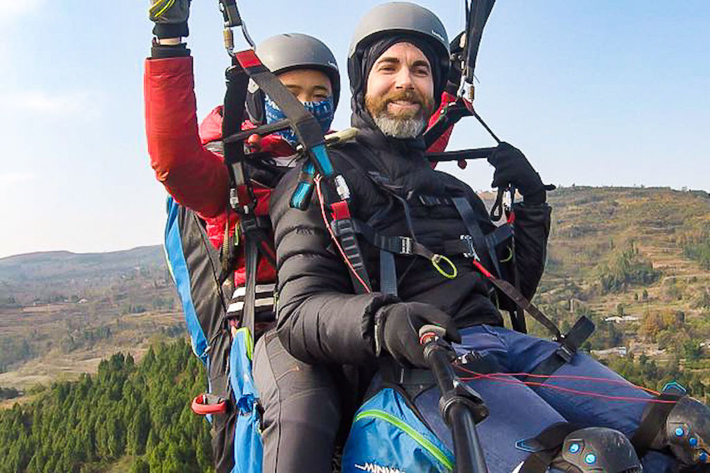 Selfie of two men paragliding over farmland