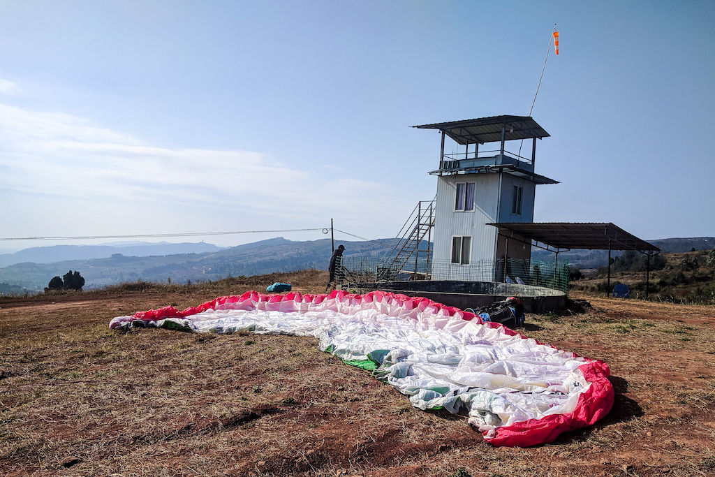 Large white parachute being readied in an open field