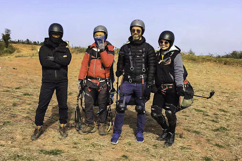 Four people standing in a field wearing paragliding harnesses
