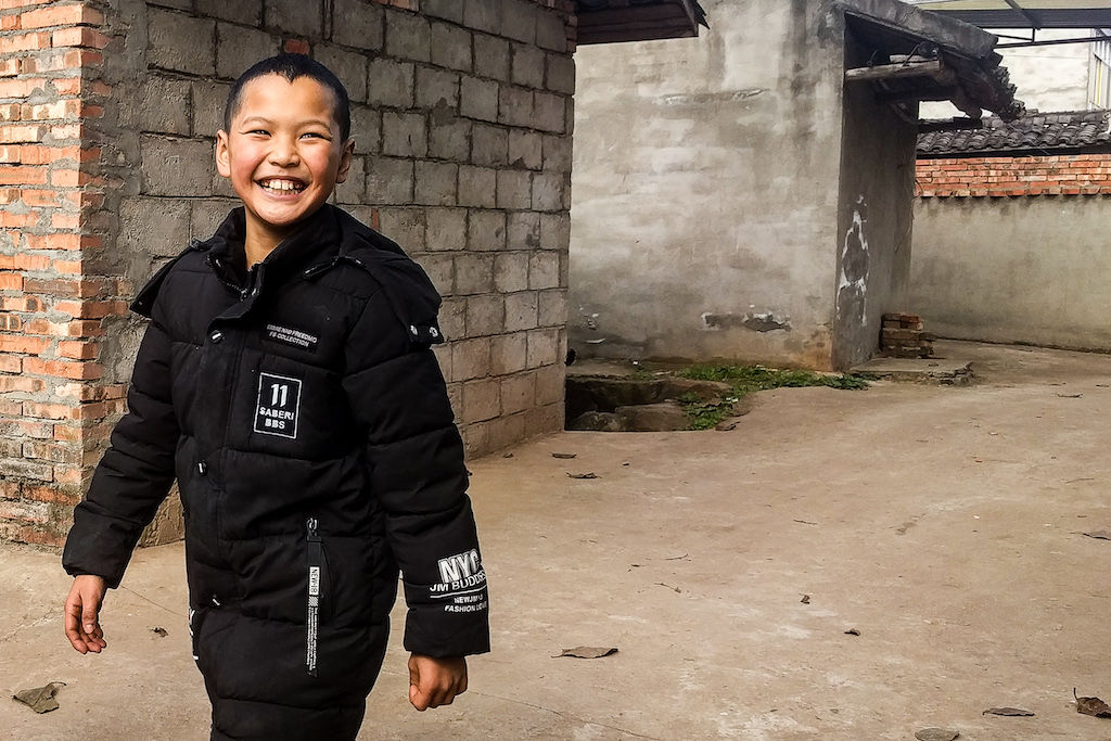 A Chinese kid in a black jacket laughing with brick buildings in the background