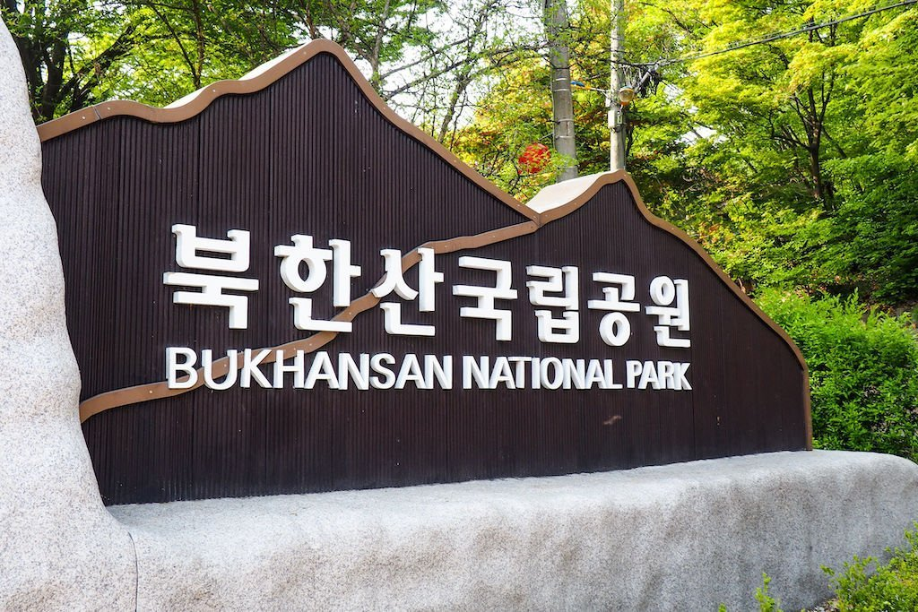 "A white sign against a black backdrop that says ""BUKHANSAN NATIONAL PARK"""