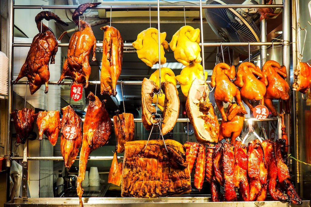 A glass window full of hanging goose, chicken, bacon, and more