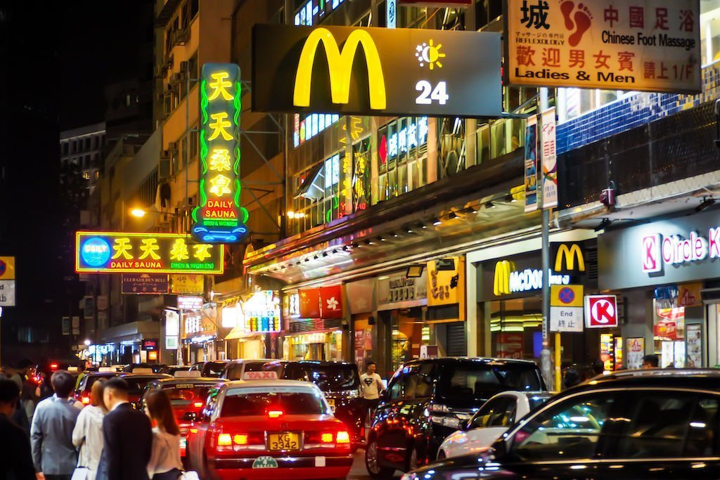 View down a Hong Kong road at night with cars, people, and neon signs