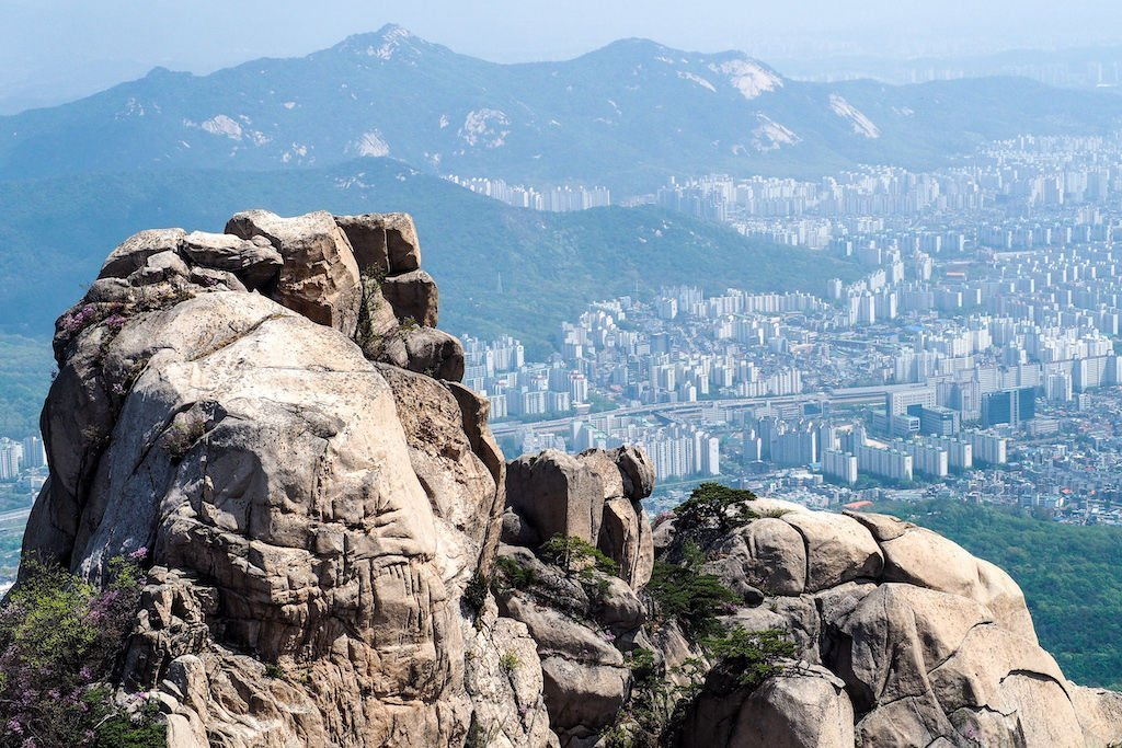 A round rock atop a mountain with the hazy outlay of Seoul below