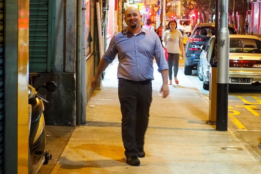 Smiling bald man walking down the sidewalk in Hong Kong