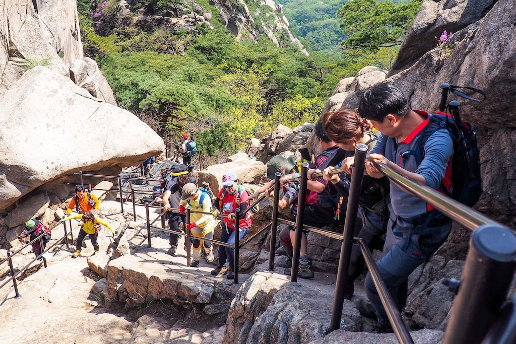 A line of hikers slowly descending a steep mountain while gripping a handrail