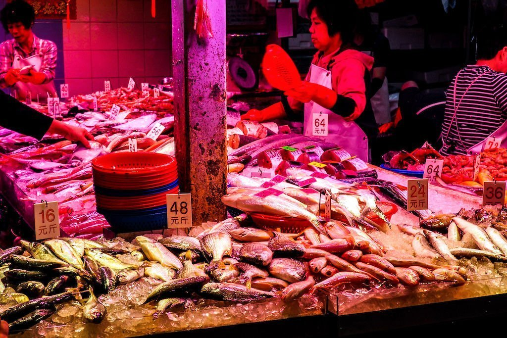 Piles of fish stacked on top of ice in a market with people working in the background