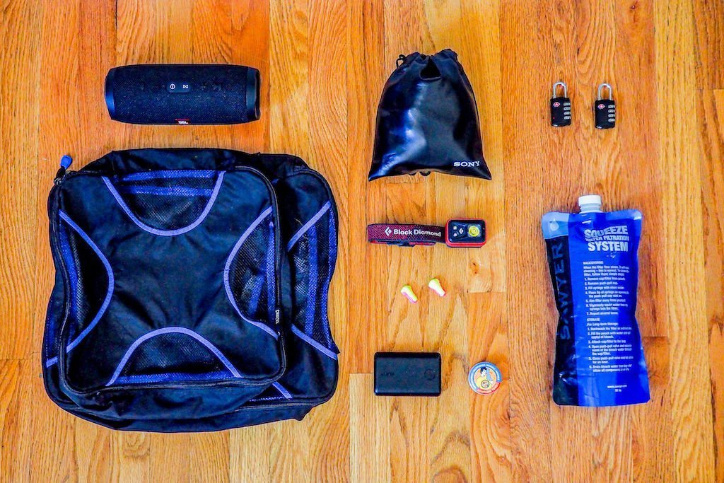 Lightweight travel packing items (speaker, headphones, water bottle) on a hardwood floor