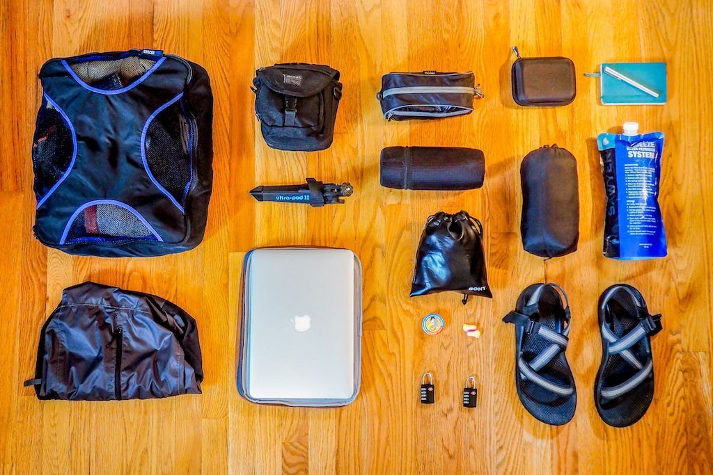 Lightweight travel and backpacking gear laid out across a wood floor