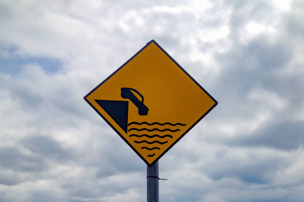 A street sign with a car driving into a body of water, a bad travel experience