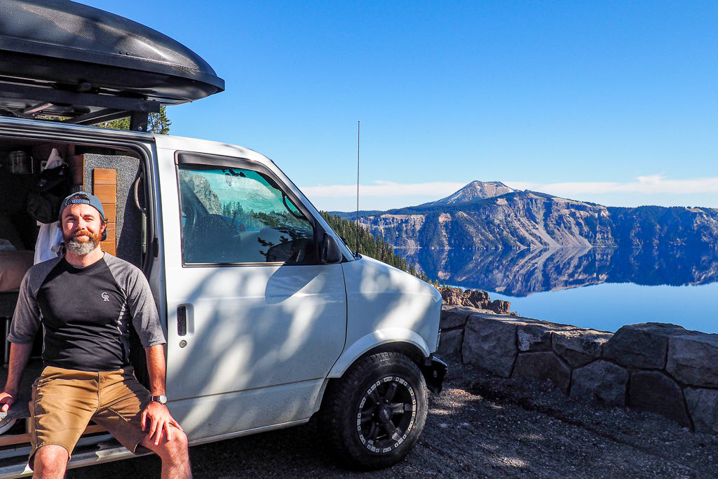 Noel against a white camper van while living full-time with Crater Lake, Oregon in the background