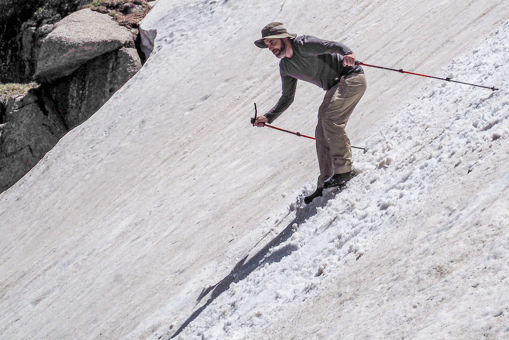 A man glissades down a snow bank with trekking poles in his hands