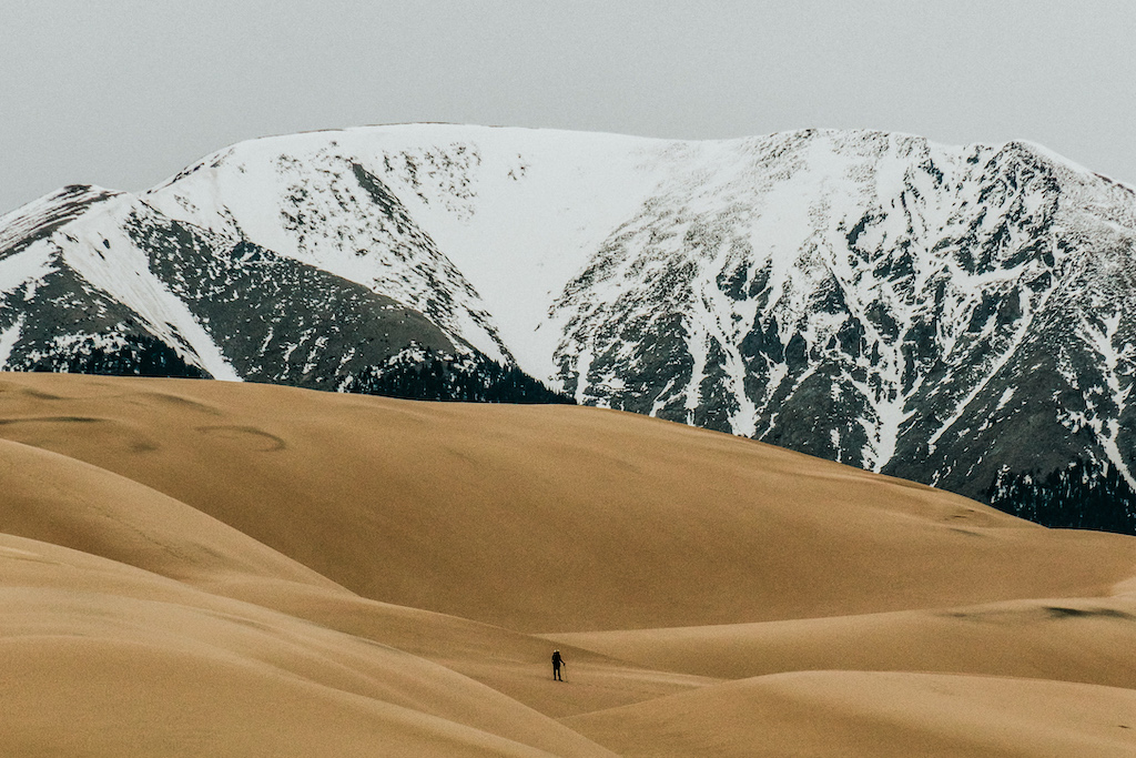 A hiker on rolling sand dunes with snowy mountains in the background