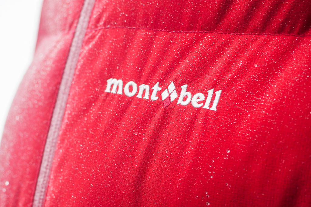 "Close up view of stitched text on a red down parka reading ""montbell"""