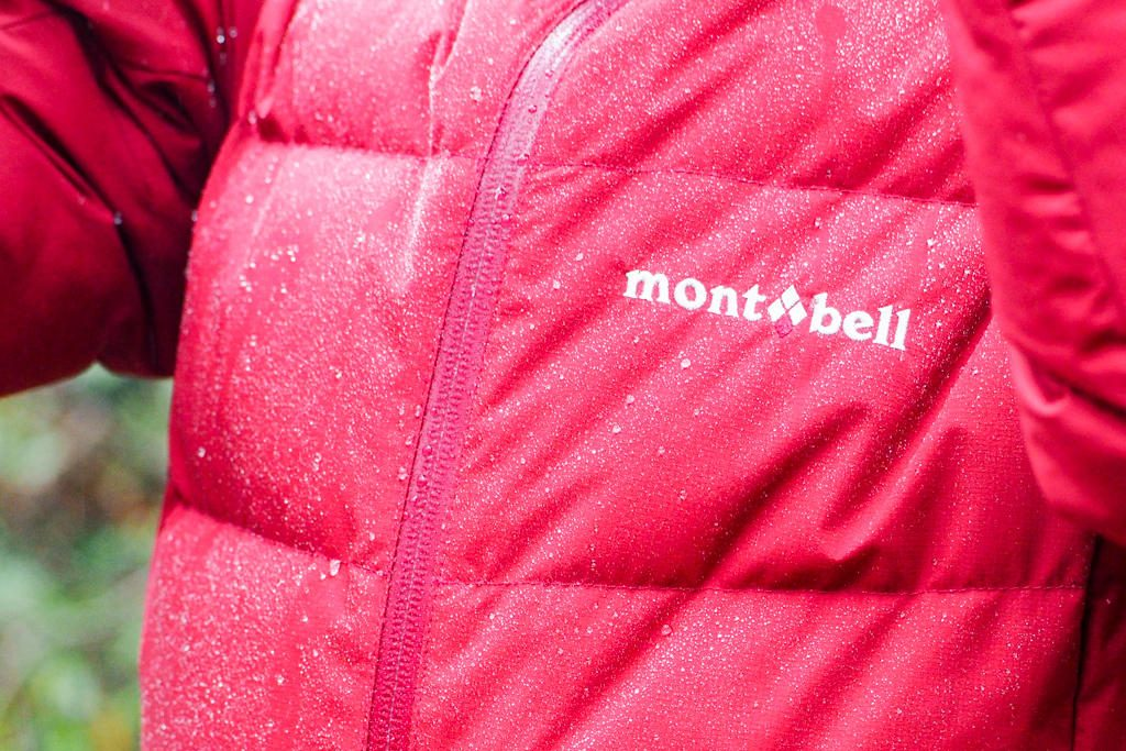 "Front view of a woman wearing a red jacket reading ""montbell"" on the front"